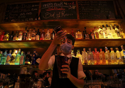 A female bartender wearing a protective face mask mixes an alcoholic drink at a bar, in Beirut