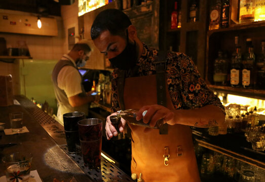 A bartender wearing a protective face mask prepares an alcoholic drink at a bar, in Beirut