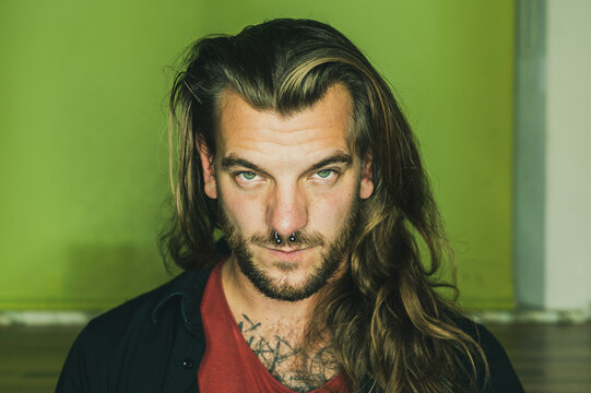 Man with long hair looks seriously at the camera