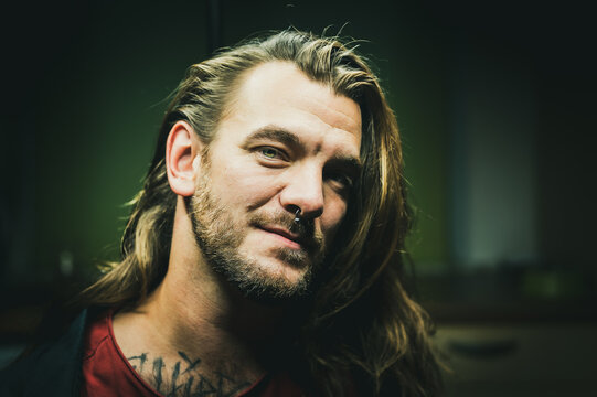 Man with long hair looks smiling at the camera. He seems to be considering.