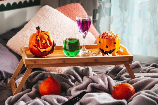 Tray on bed with halloween decor, popcorn, drinks and remote controller. Halloween background for movie night, pastime idea for holiday