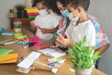 Photo sur Plexiglas Dinosaurs School teacher helping children in classroom while wearing safety masks during coronavirus outbreak- Focus on boy's face