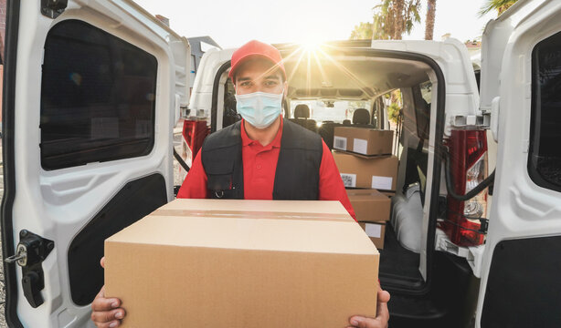Courier man delivering online ordered packages wearing face mask during coronavirus outbreak - Focus on cardboard box