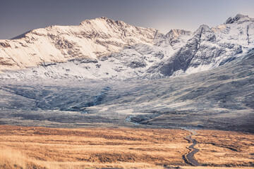 Path and winter scenery in the mountains - snow covered rocky summits of Cuillins in Glenbrittle, Isle of Skye, Scotland