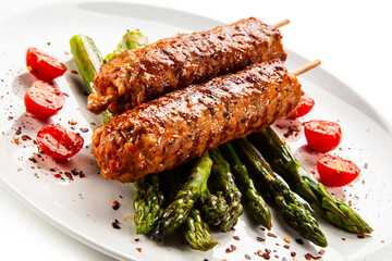 Fried meat with asparagus on white background