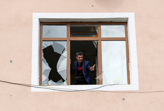 A man cleans the broken parts of his window after a ceasefire begins during the fighting over the breakaway region of Nagorno-Karabakh in the city of Terter