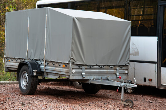 A car trailer covered with a gray tarpaulin in an unpaved parking lot.