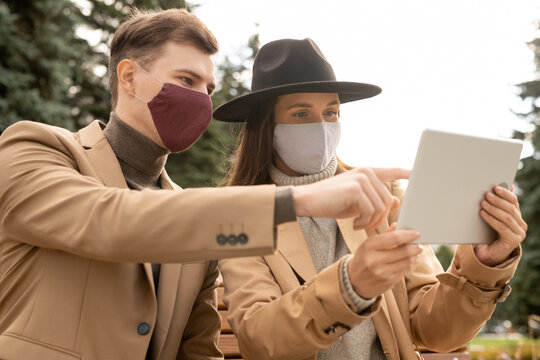 Young stylish couple in protective masks and stylish casualwear resting in park