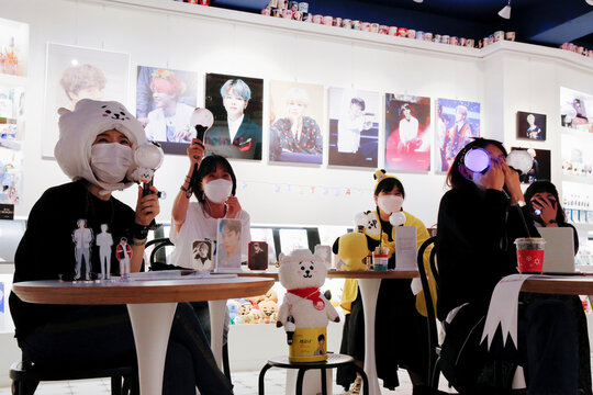 Fans of K-pop idol boy band BTS enjoy as they watch a live streaming online concert, wearing a protective masks at a cafe, in Seoul