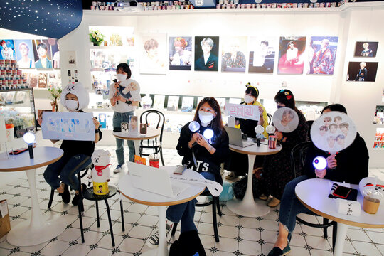Fans of K-pop idol boy band BTS watch a live streaming online concert, wearing a protective masks at a cafe, in Seoul