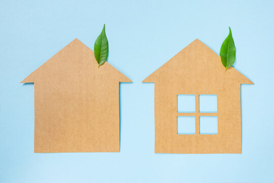 Houses made of craft paper and green leaves of a plant on a light blue background. Eco-friendly home concept, healthy lifestyle, zero waste.