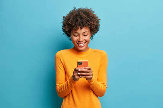 Online lifestyle concept. Cheerful good looking woman with Afro hair sends text messages via mobile phone dressed casually searches gifts for holiday in internet uses smartphone app browses webpage