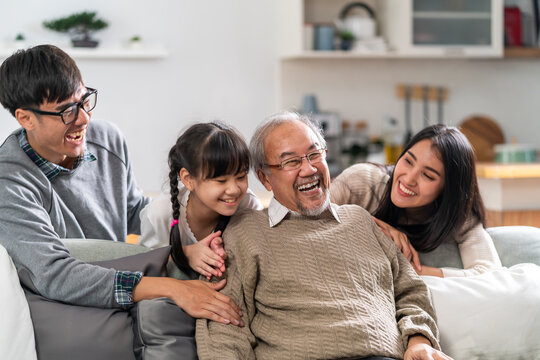 Happy multigenerational asian family portrait in living room