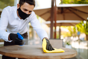 Cleaning and disinfection of table to prevent COVID-19. Waiter in  protective face mask and gloves ...