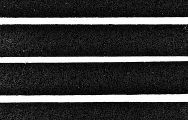 Paski cienkiej czarnej gumy na jasnym tle.
