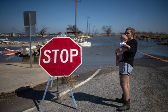 Woman holds son after visiting family business destroyed by Hurricane Delta in Creole, Louisiana
