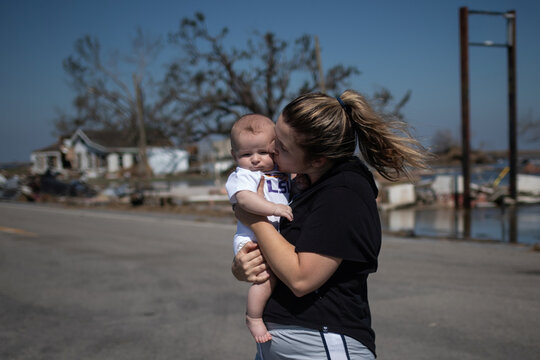 Woman kisses son after surveying family business destroyed by Hurricane Delta in Creole, Louisiana