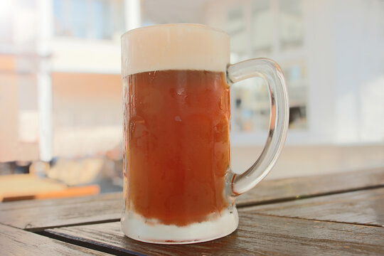 Close up of a cold fresh draft beer in a large glass with beer foam standing an a wooden table in a beer garden outside in summer