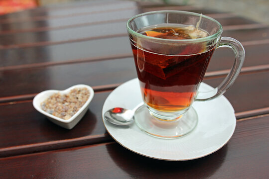 Glass cup of black tea including tea bag and sugar