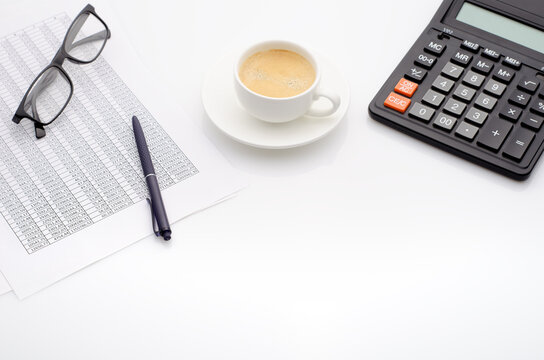 Accounting business concept. Desktop with cup of coffee, calculator, glasses and spreadsheet.