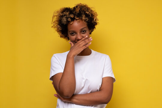 Young african woman giggles covering her mouth with hand, hiding her emotion