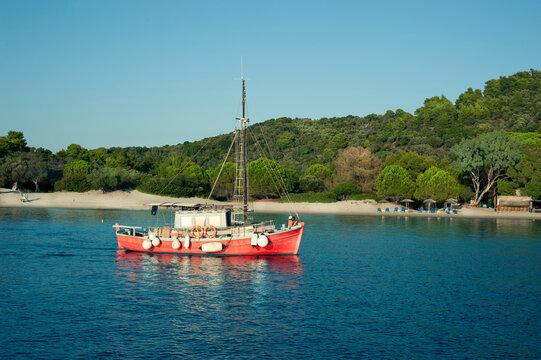 Red sailboat off coast of Skiathos Island, Greece