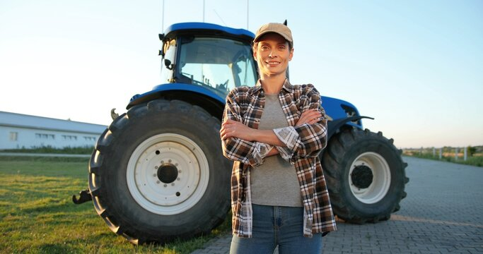 Portrait shot of beautiful Caucasian young woman in cap standing outdoor at farm with big tractor machine on background and smiling joyfully to camera. Pretty happy female farmer in field. Agriculture