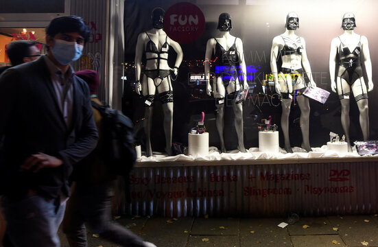 People walk in front of a shop window at famous red-light-district Reeperbahn during the spread of the coronavirus disease (COVID-19), in Hamburg