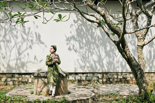 Beautiful young woman in ao dai dress sitting in garden with bouquet of lotus flowers and looking away