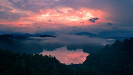 Aerial view of sunrise color reflected on the surface of a lake. Low hanging clouds added a dramatic effect to the scene.