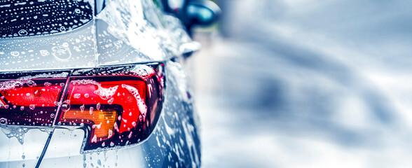 Obraz Manual car wash with white soap, foam on the body. Washing Car Using High Pressure Water. - fototapety do salonu