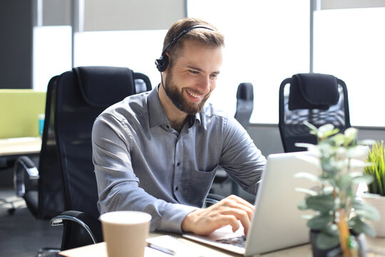 Smiling male call-center operator with headphones sitting at modern office, consulting online information in a laptop, looking up information in a file in order to be of assistance to the client.