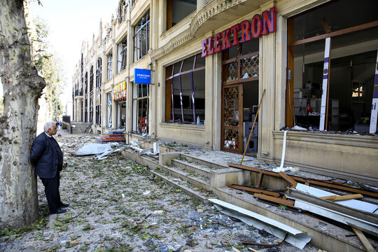 A shop owner stands in front of his store at the blast site hit by a rocket during the fighting over the breakaway region of Nagorno-Karabakh in the city of Ganja