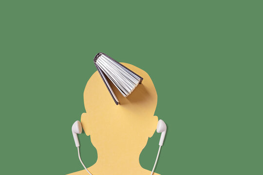 A silhouette of a man's head, next to a headset, and a book on top. Audiobooks, lectures, podcasts, teaching concept. Minimalism, copy space.