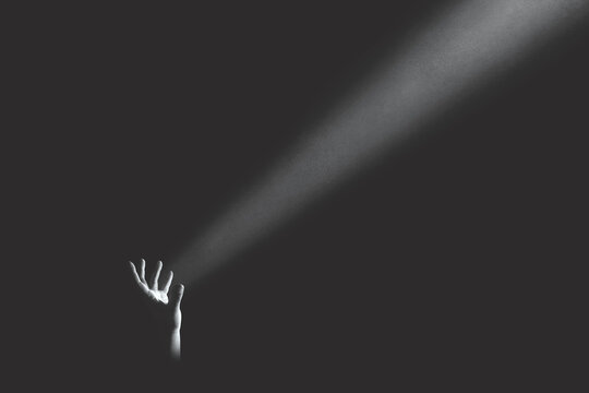 hand holding light ray in the darkness, hope concept