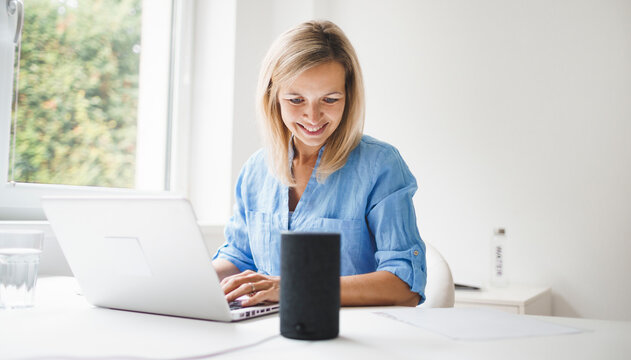 beautiful young and blond woman is talking to her smart speaker and is working at home during corona lock down