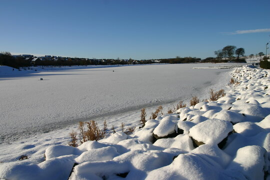 Looking across a frozen lake with rocks in the foreground