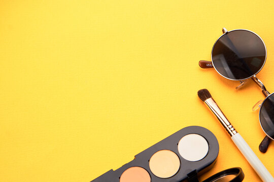 Professional eyeshadows and makeup brushes on a yellow background make-up decoration