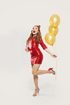 Happy surprised woman with yellow balloons standing on white background, Christmas or New Year party concept