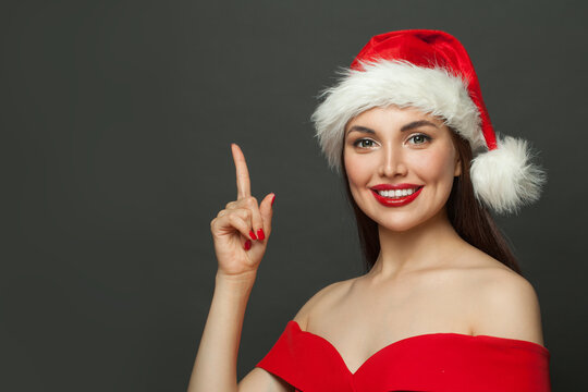 Happy woman Santa pointing up on black. Christmas holiday and New Year party portrait