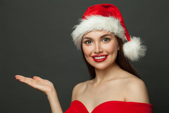 Happy woman Santa holding empty open hand on black Christmas holiday and New Year party background