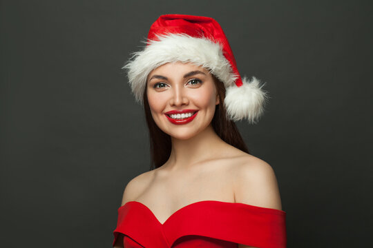 Beautiful woman Santa smiling on black background. Christmas holiday and New Year party portrait