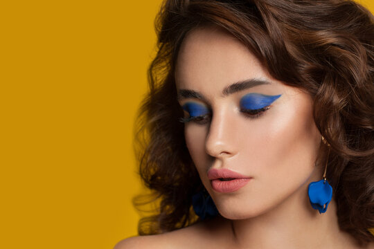 Beautiful woman with blue eyeshadow makeup and curly hair on yellow background