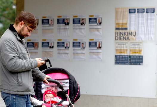 A man checks his phone next to a polling station during general election in Trakai