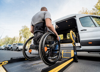 Photo sur Plexiglas Dinosaurs A man in a wheelchair moves to the lift of a specialized vehicle