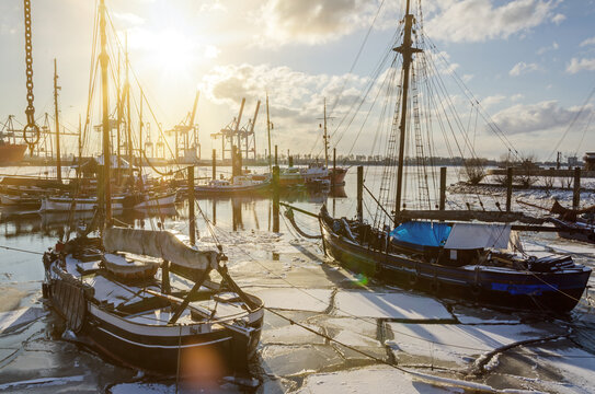 Historic shipping boats in the harbor in Hamburg Övelgönne in winter during scenic sunset