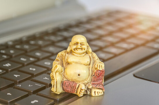 Buddha statue on computer keyboard symbolizing stress reduction and mindfulness