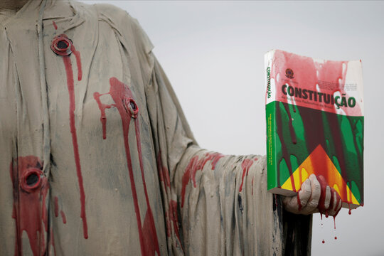 An actor holds a book of the Brazilian constitution, during a protest against Brazil's President Jair Bolsonaro and racism, in Brasilia