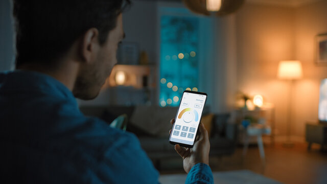 Young Handsome Man Gives a Voice Command to a Smart Home Application on His Smartphone To Change Light Temperature and Set a Comfortable Lighting. It's a Cozy Evening in Living Room.