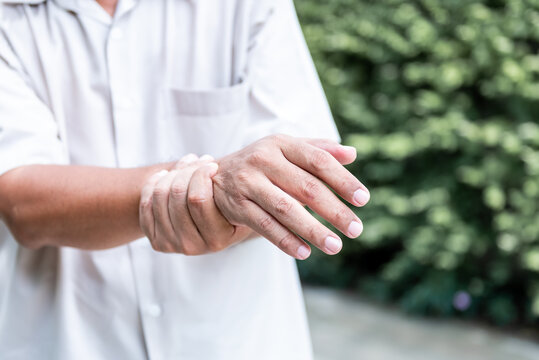 Patients elderly wrist pain hands, due to a nervous system illness and paralysis, On blur background, to health care concept.